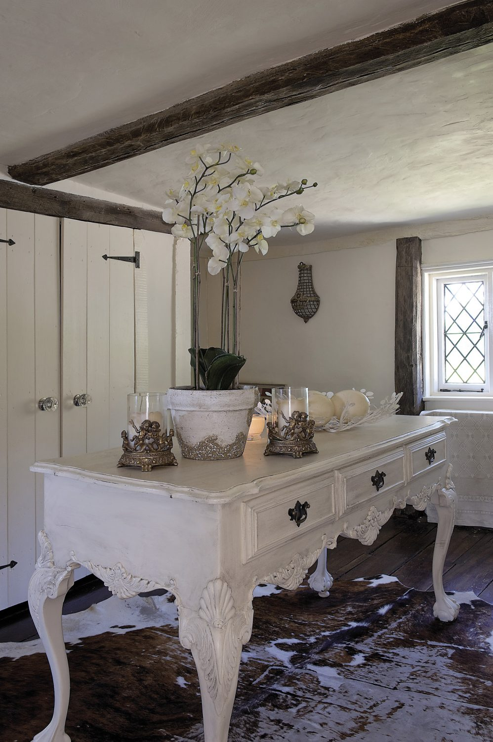 The landing is a surprisingly large space and Andrew has cleverly added an element of drama by keeping the wooden floor uncluttered apart from a flamboyantly carved table placed in the centre of the room. A wall of built-in wardrobes enables the area to function as Andrew's dressing room