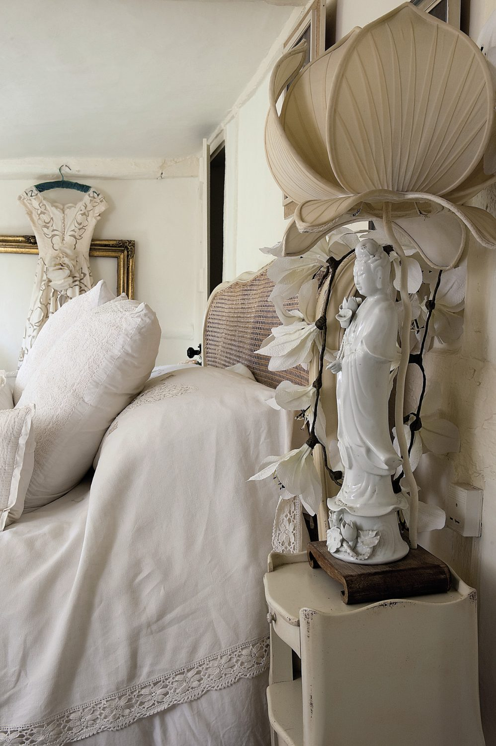 In the second bedroom again there are plenty of decorative flourishes. Ornate gilded and mirrored sconces hang above an exuberantly carved console table. Embroidered shawls cover the radiators and a vintage cutwork wedding dress is displayed on one wall