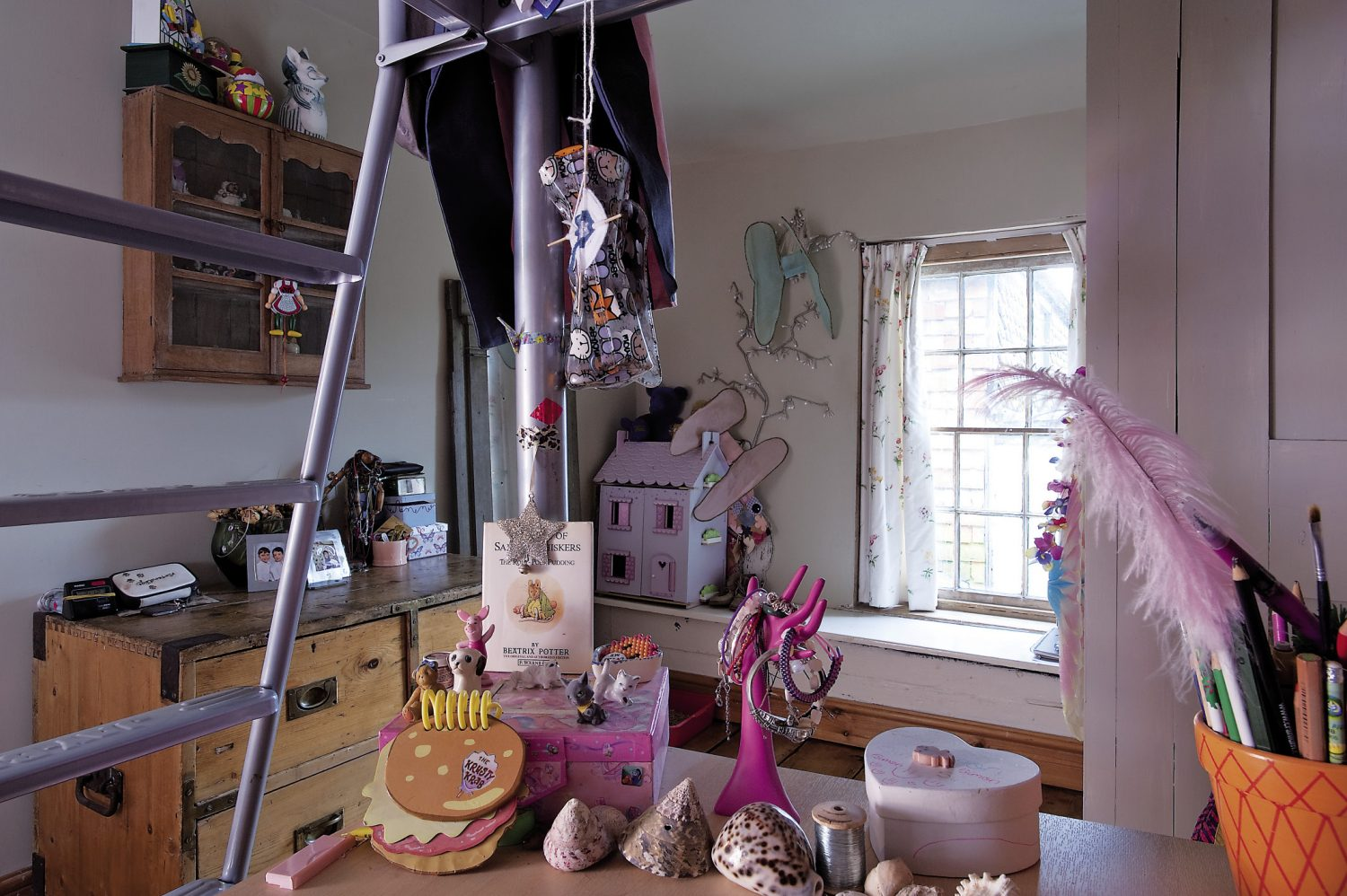 Brad and Jackie's daughters share a room that is full of new and vintage toys. A dolls' house stands by the window that is framed by curtains made from a Georgian style spriggy floral print. The girls' desk already shows signs of an enthusiasm for collecting things too, with shells and found objects carefully arranged in groups