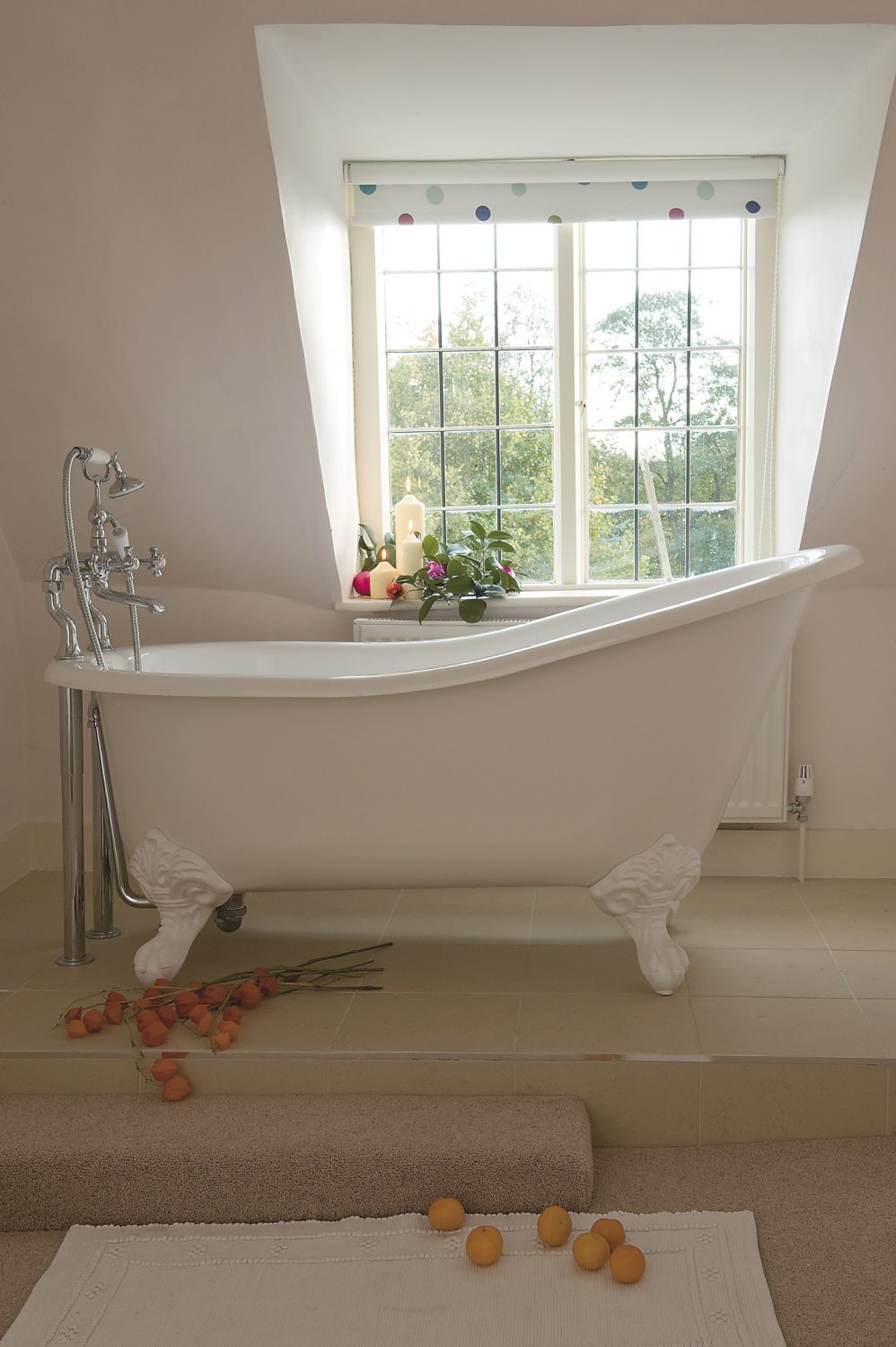 """a glorious, free-standing bath sits near a window giving a beautiful view of the garden. Jemima says: """"this is the best position for a bath ever – such a wonderful view""""..."""