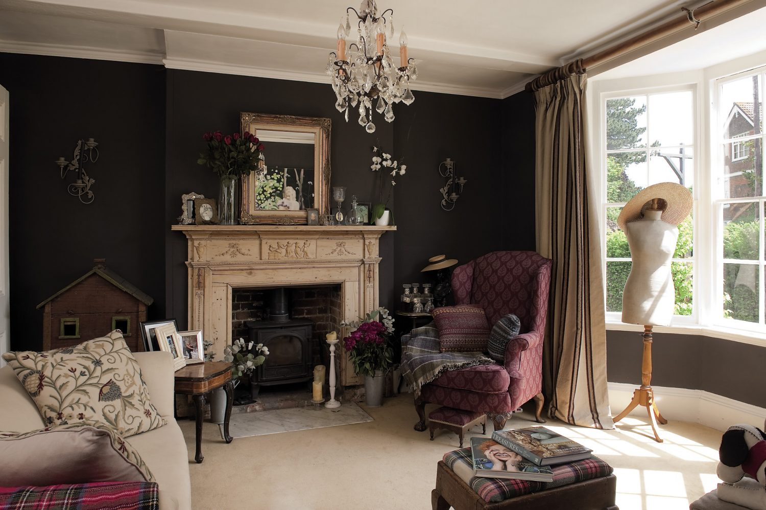 """Across the hallway, the drawing room has been painted a dramatic mocha. """"It's Flamant paint from Belgium,"""" says Pippa. """"Their colours are really intense and I think this one's called Lune de Noir."""" An antique crystal chandelier reflects the sunlight around the room"""