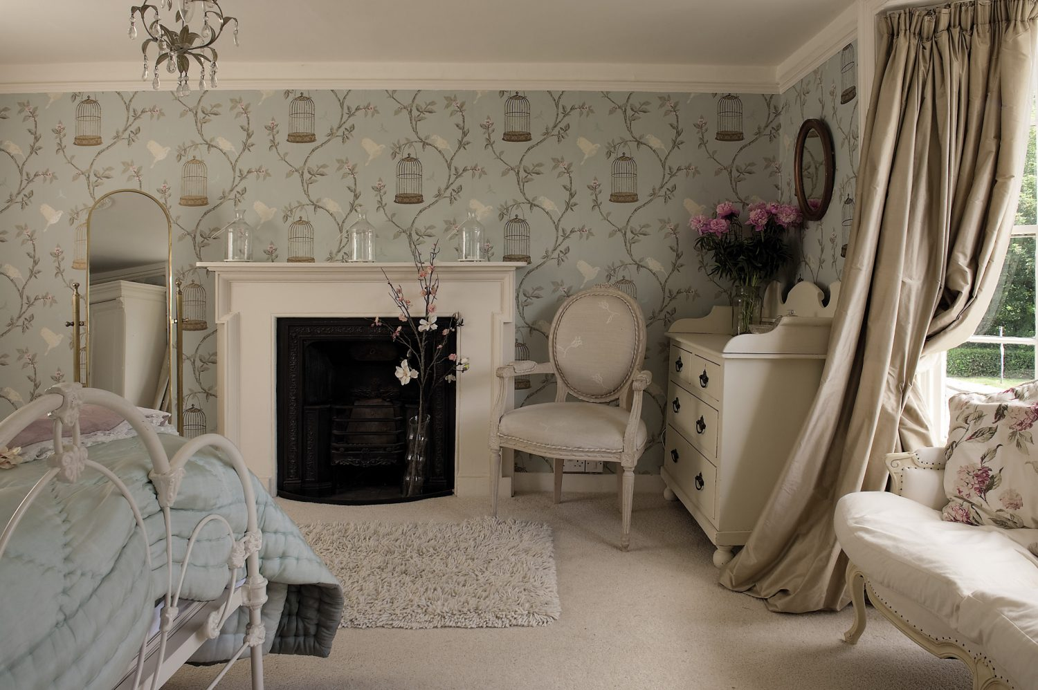 Along the corridor is the 'Chambre Jolie', papered in 'Birdcage Walk' by Nina Campbell. A French 18th century style sofa occupies the space in the bay window and is framed on either side by café au lait-coloured silk curtains. White painted furniture maintains the feeling of light and the iron bed is dressed with a handstitched eau de nil silk quilt