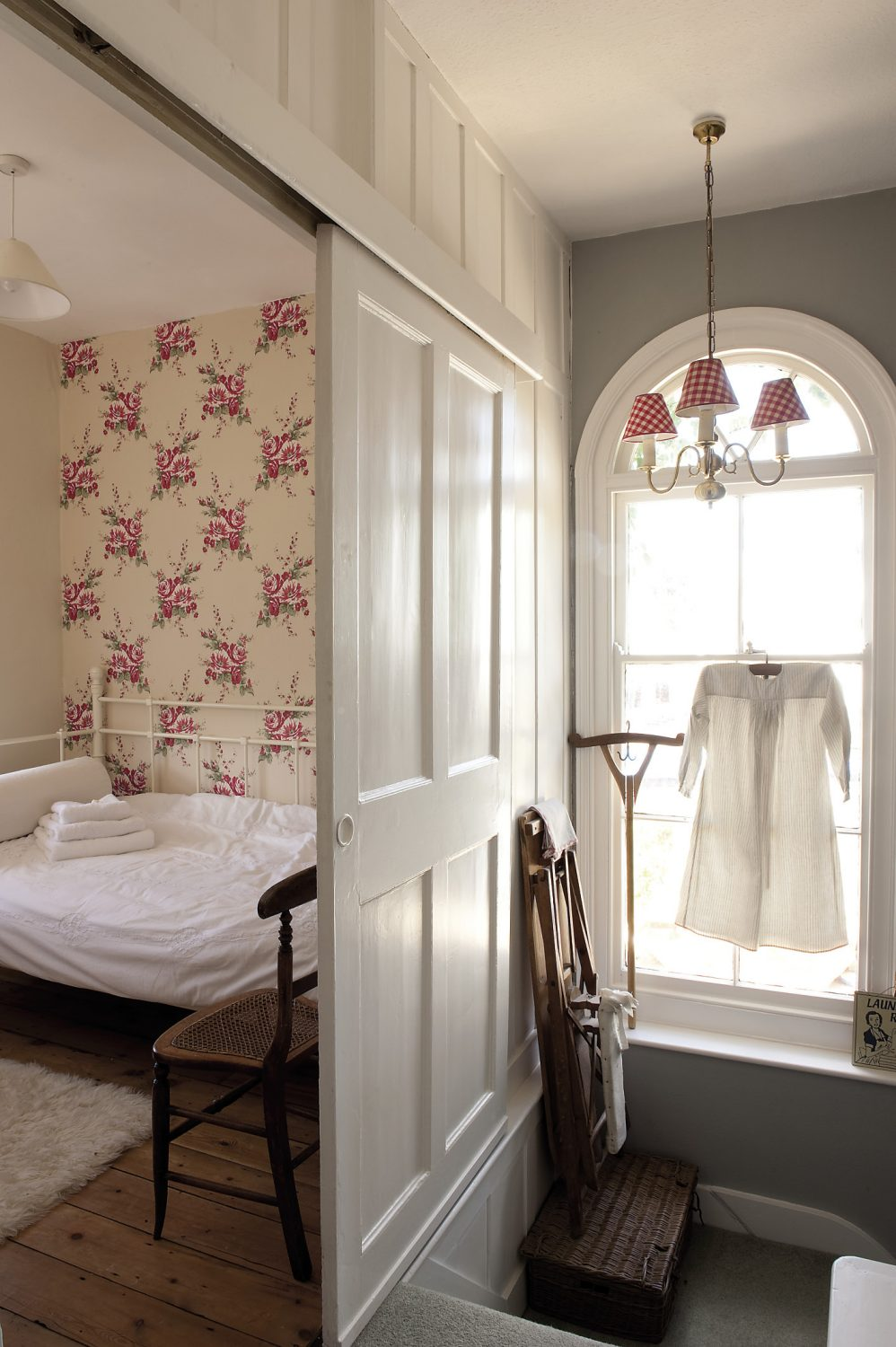 Just across the corridor, behind a sliding door and tucked away in the tower, is a small wood-panelled bedroom that's very popular with visiting children. There is an iron daybed and the wall behind it is papered with jolly, striped red and white roses...