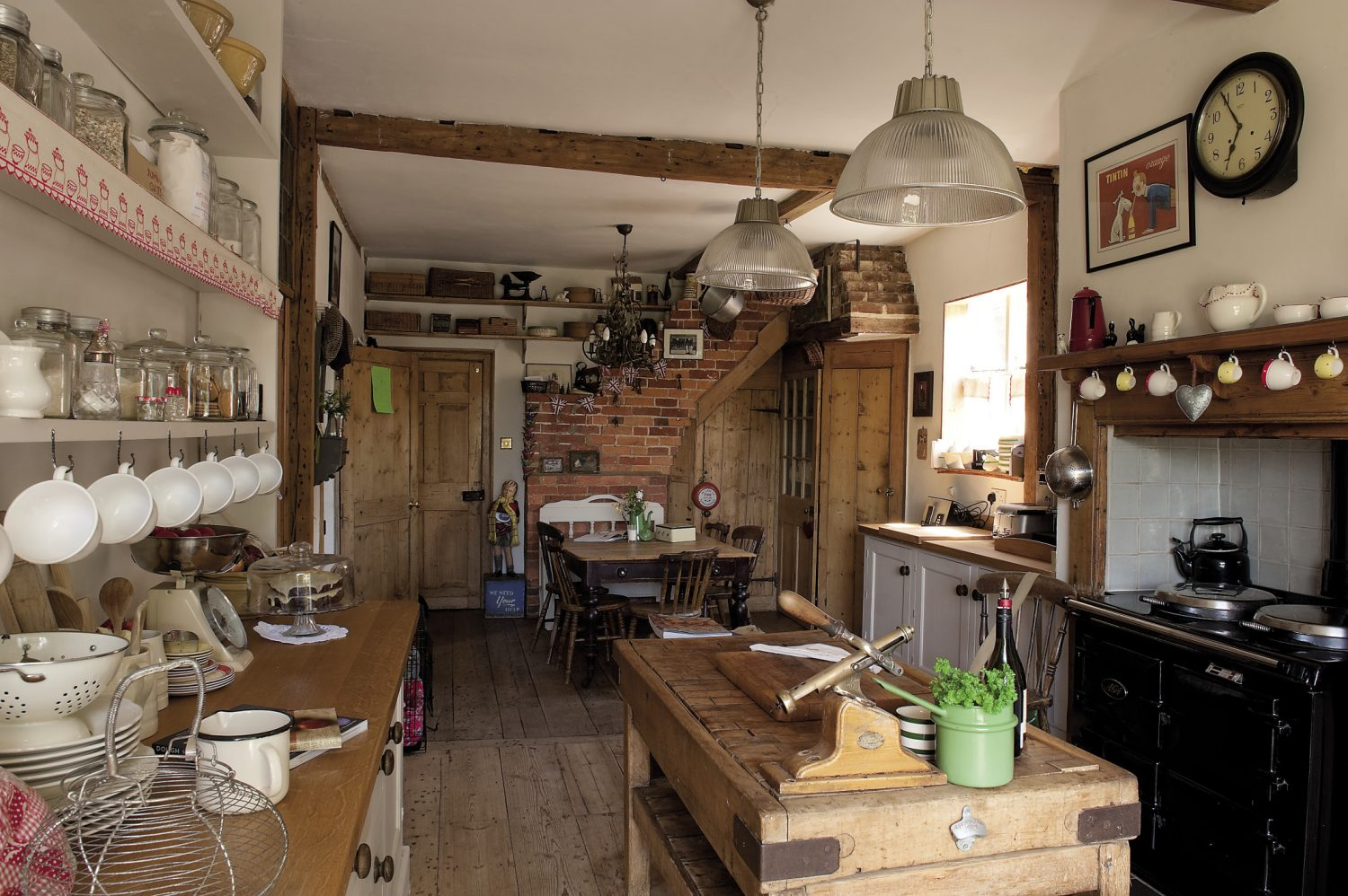 The kitchen is evidently the hub of the house. Simple in tone, it is very much a working environment, with a black enamel Aga and a deeply scored butcher's block in the centre
