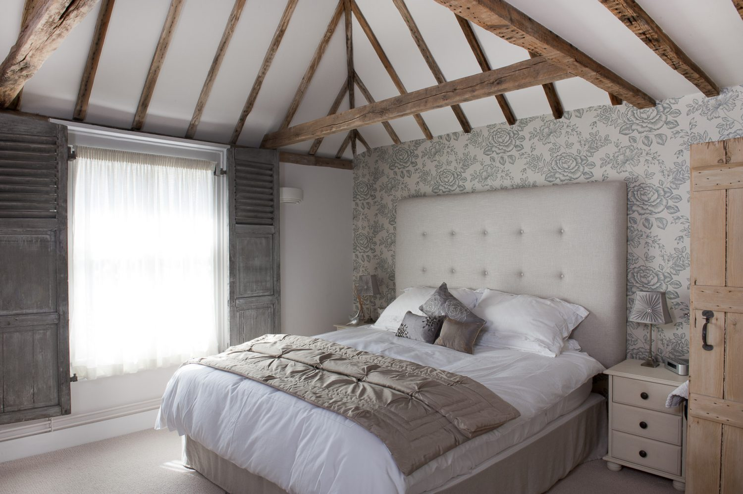 In the glamorous master bedroom a bed dressed with cotton and satin bedclothes is set against a feature wall of Sanderson wallpaper. Plain muslin is draped across the window for privacy during the day and a pair of working shutters with louvred panels can be drawn across at night