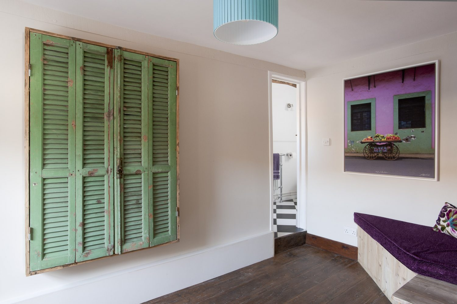 In the study a large photograph printed on canvas echoes the vivid purple and green soft furnishings that Rosemary has used in the room. The bathroom next door features black and white diamond floor tiles, a roll top bath and a Savoy style pedestal basin...