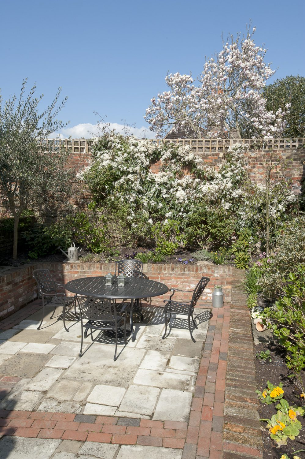 The peaceful, sheltered courtyard features high walls covered in climbing roses and fragrant clematis armandii. Raised brick beds are planted with hydrangeas, camellias, lavender and pinks