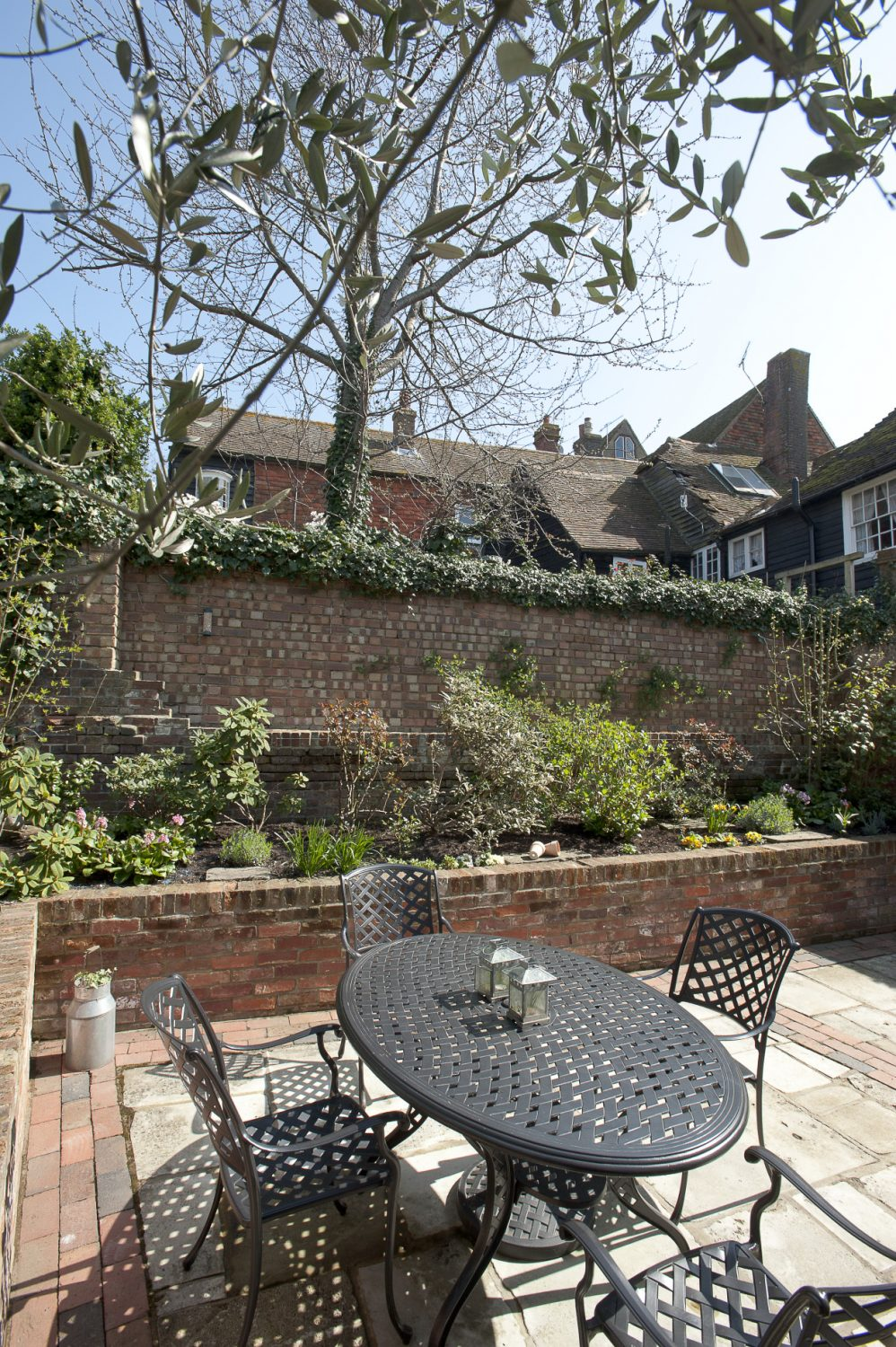 Raised brick beds are planted with hydrangeas, camellias, lavender and pinks