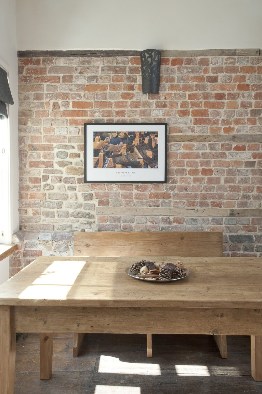 In one corner of the reception room stands a long scrubbed pine refectory table unadorned apart from a bowl of fragrant pine cones and cinnamon sticks. Set against the bare brick wall, it has an honest simplicity.