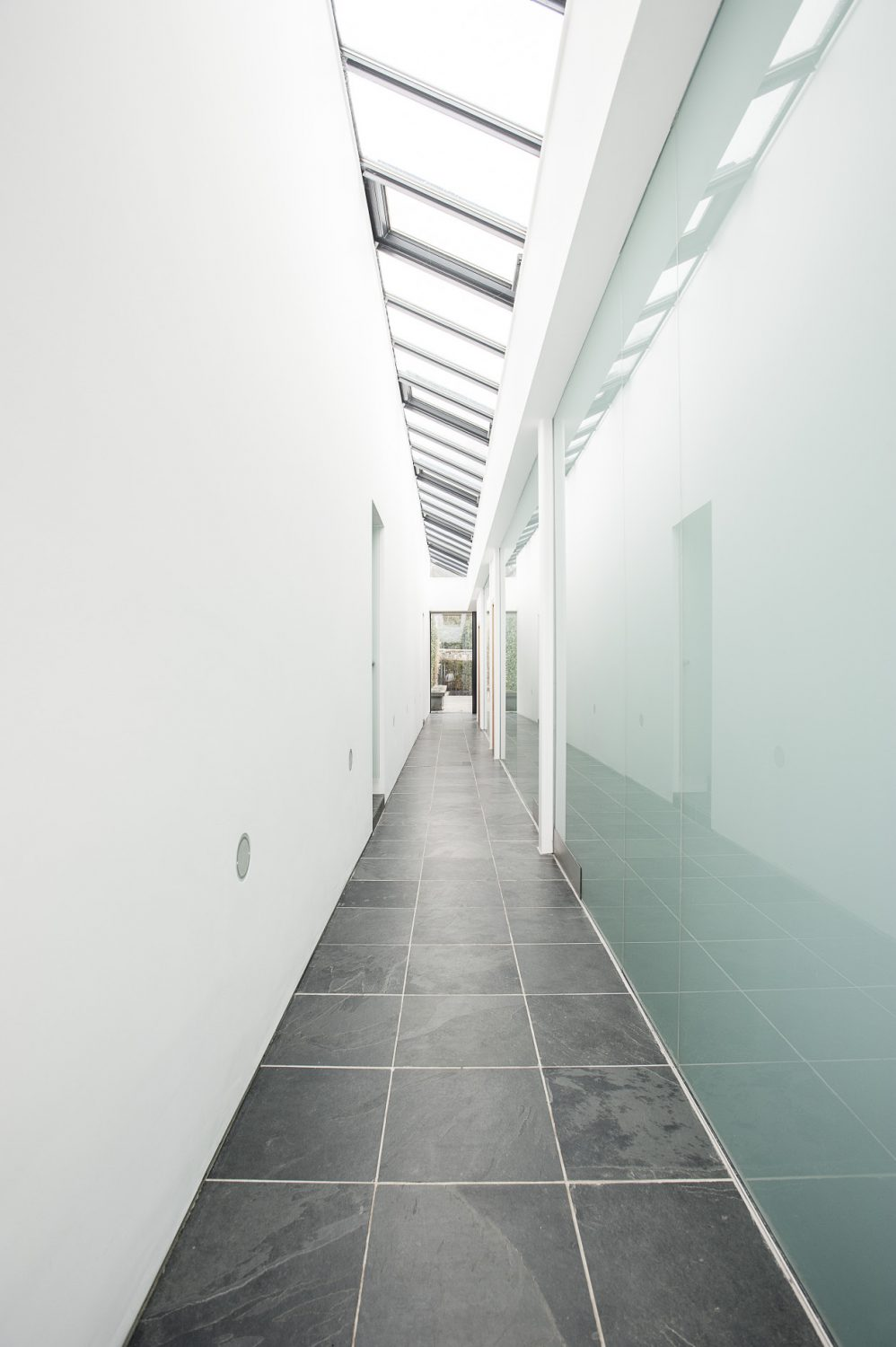 A glazed passageway acts as the spine of the building and separates the contemporary glass part of the building from the original potting sheds