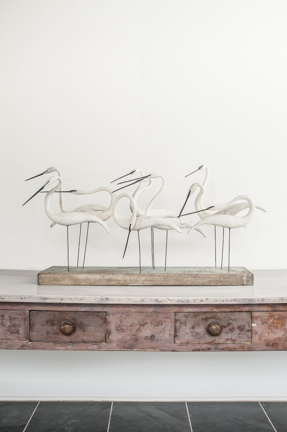 A driftwood sculpture of a group of egrets by Essex artist Guy Taplin stands on a long distressed five-drawer table from a Liverpool convent in the hallway