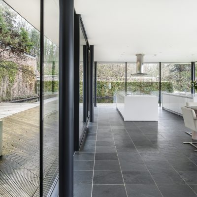The Walled Garden is essentially three spaces – two conjoined rectangular glass pavilions, one behind the other. Visitors approach between two shallow pools, strategically placed to reflect the glass portion of the building, day and night