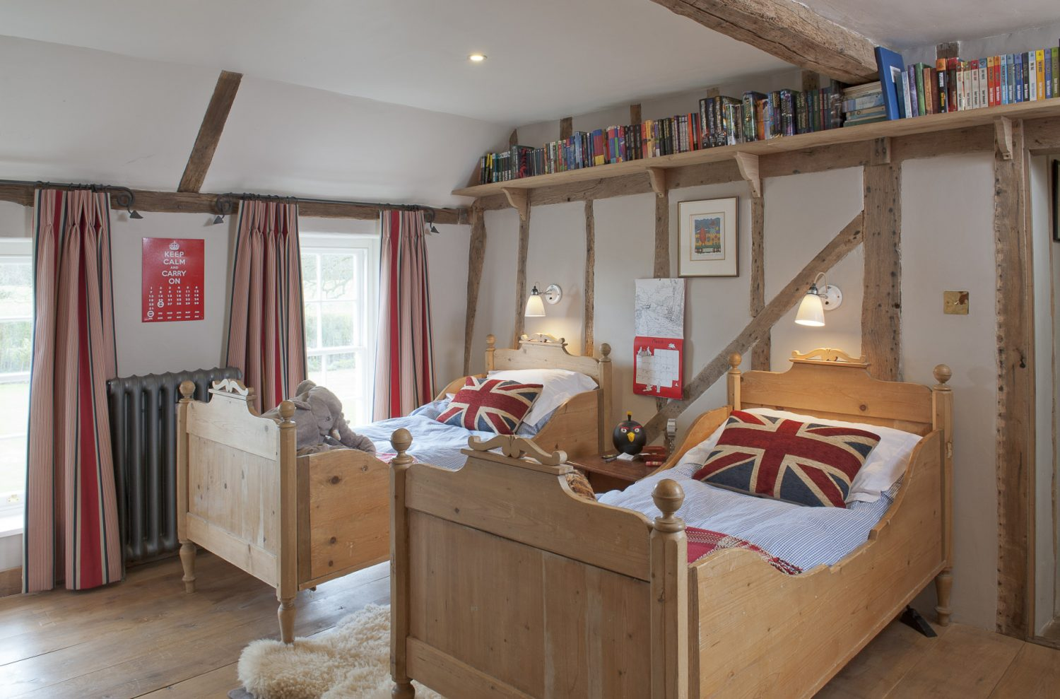 In Oscar's room, further along the landing, twin pine sleigh beds are covered with blue and white gingham quilts, Union Jack cushions and red and white checked blankets