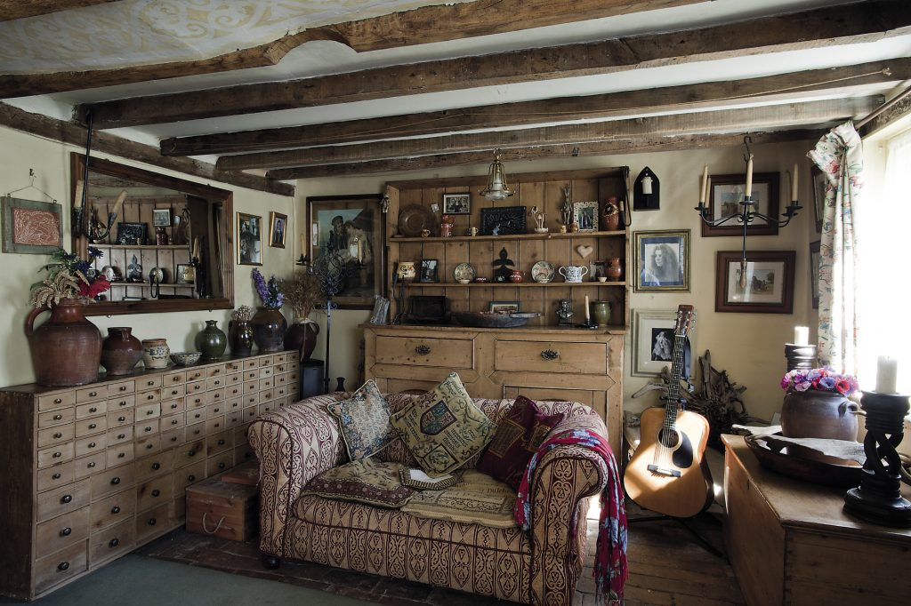 """A long set of drawers fills the length of one wall in the front parlour. """"There are 84 drawers, I think they're from an old ironmonger's and yes, I have filled them all. I collect all sorts of things, pine cones, shells, skulls and rosehips, anything that I think is interesting I suppose."""" There are several guitars waiting to be played and a Windsor chair by the fire"""