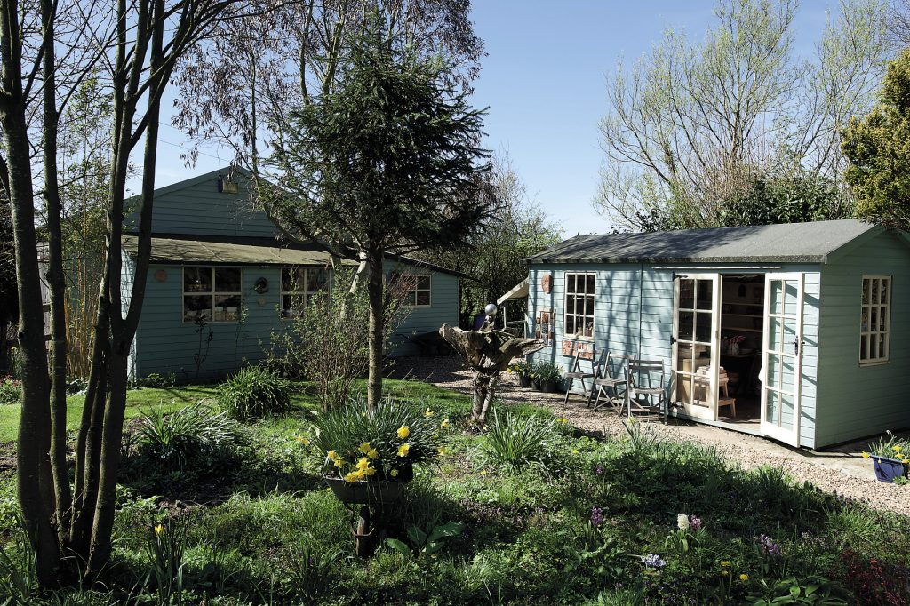 The beautiful garden on a sunny April afternoon. Two blue and white painted wooden studios occupy one end. The larger of the two is full of Claudine's 400 moulds that she uses, whilst the other building houses the completed pots