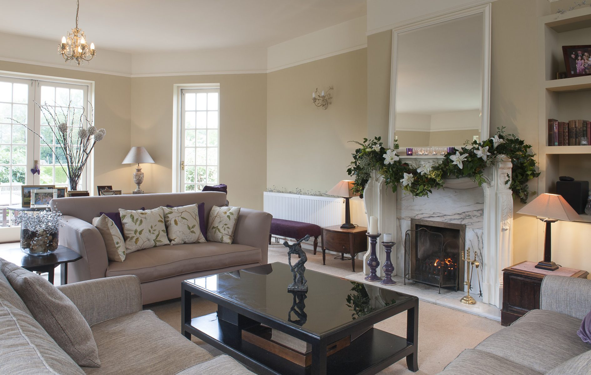 A glossy piano black coffee table stands in the centre of the spacious drawing room between the three sofas