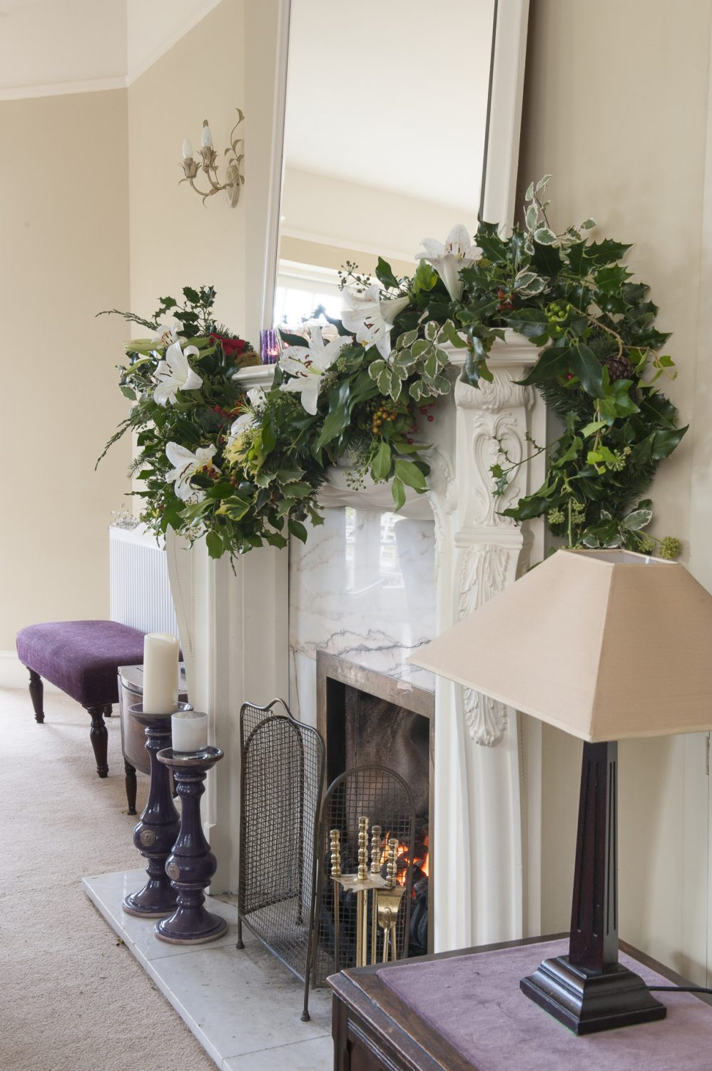 In the drawing room a marble fireplace has been adorned with a swag of berried holly, dark evergreen leaves and white stargazer lilies. The Christmas tree has been decorated with purple and gold ornaments