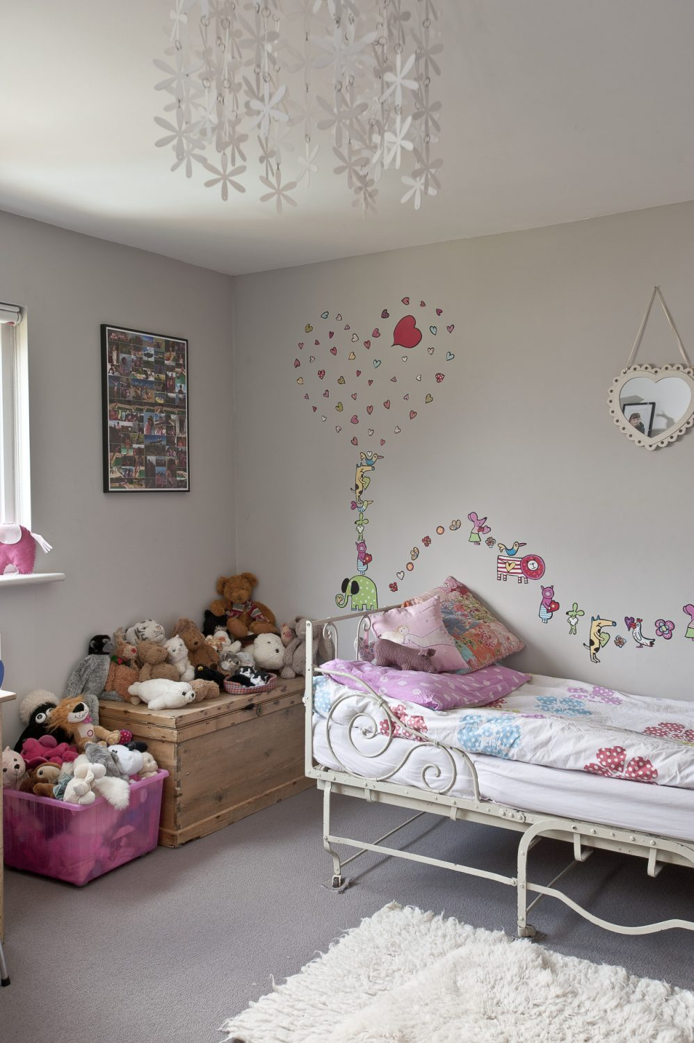 The couple's daughter's room is the perfect nine-year-old girl's room with a pretty wrought-iron bed and a stripped pine double old school desk