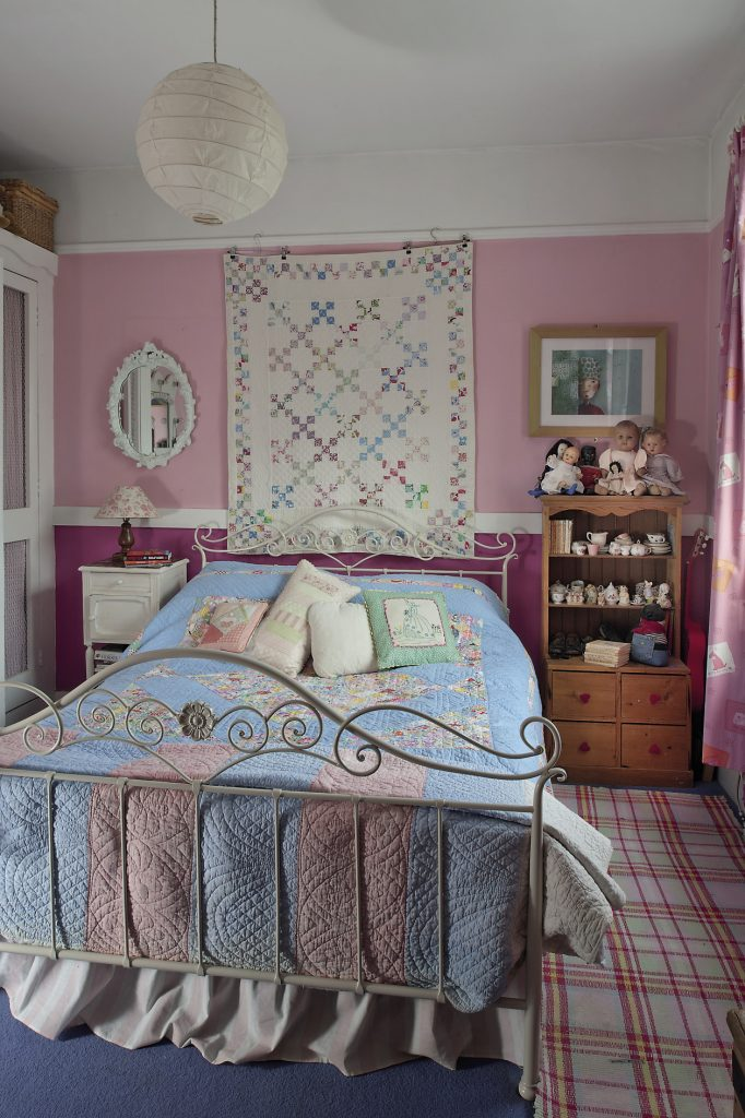 Daughter Harriet's bedroom holds a double bed covered with vintage and homemade quilts. There is a child-sized Welsh dresser, one of four that Phil made for all the children
