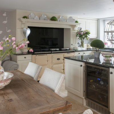 Claire's kitchen is light and warm in tone, with ivory painted kitchen units and a pale limestone floor. The walls are painted pebble grey and there are panels of a flamboyant, Cole & Son pink flamingo wallpaper