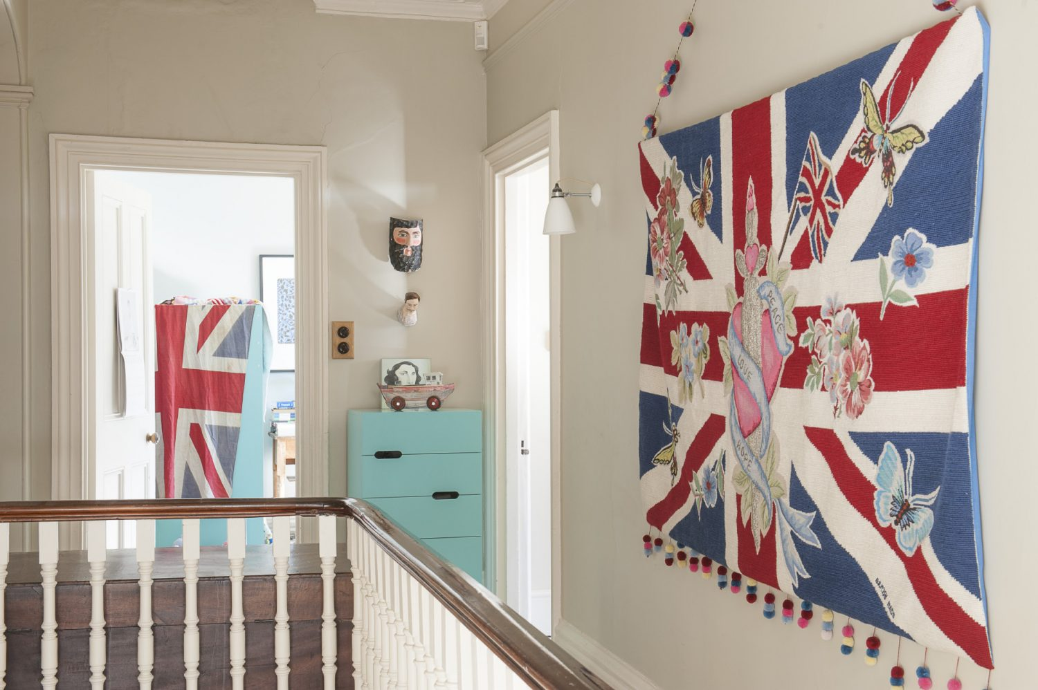 A giant embroidered and beaded Union Jack tapestry hangs boldly on one wall, whilst a comfy armchair is placed next to a set of full-to-bursting bookshelves