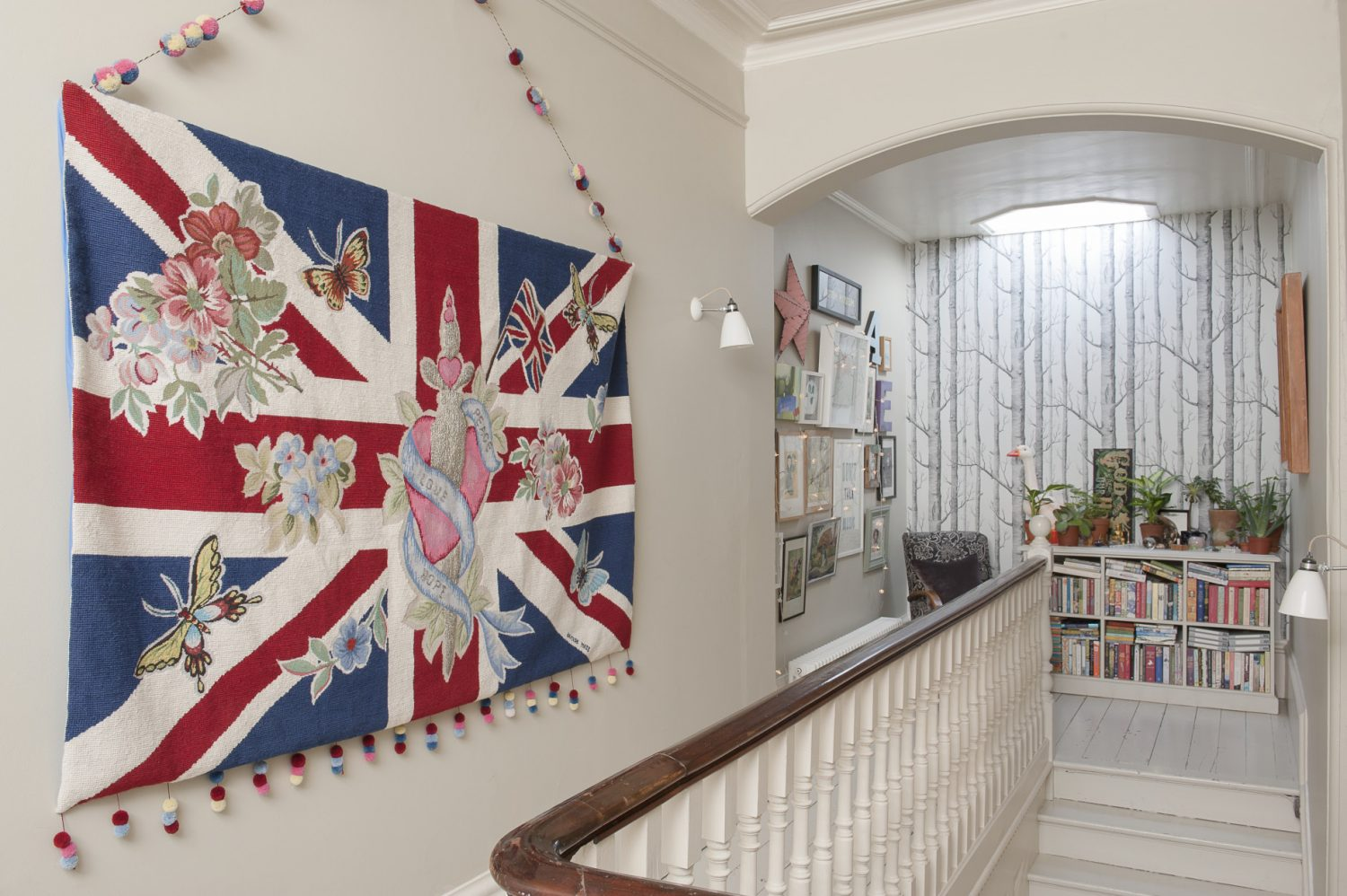 One end of the landing is papered in 'Woods' by Cole & Son and looks rather like a forest of bare birch trees. A giant embroidered and beaded Union Jack tapestry hangs boldly on one wall, whilst a comfy armchair is placed next to a set of full-to-bursting bookshelves