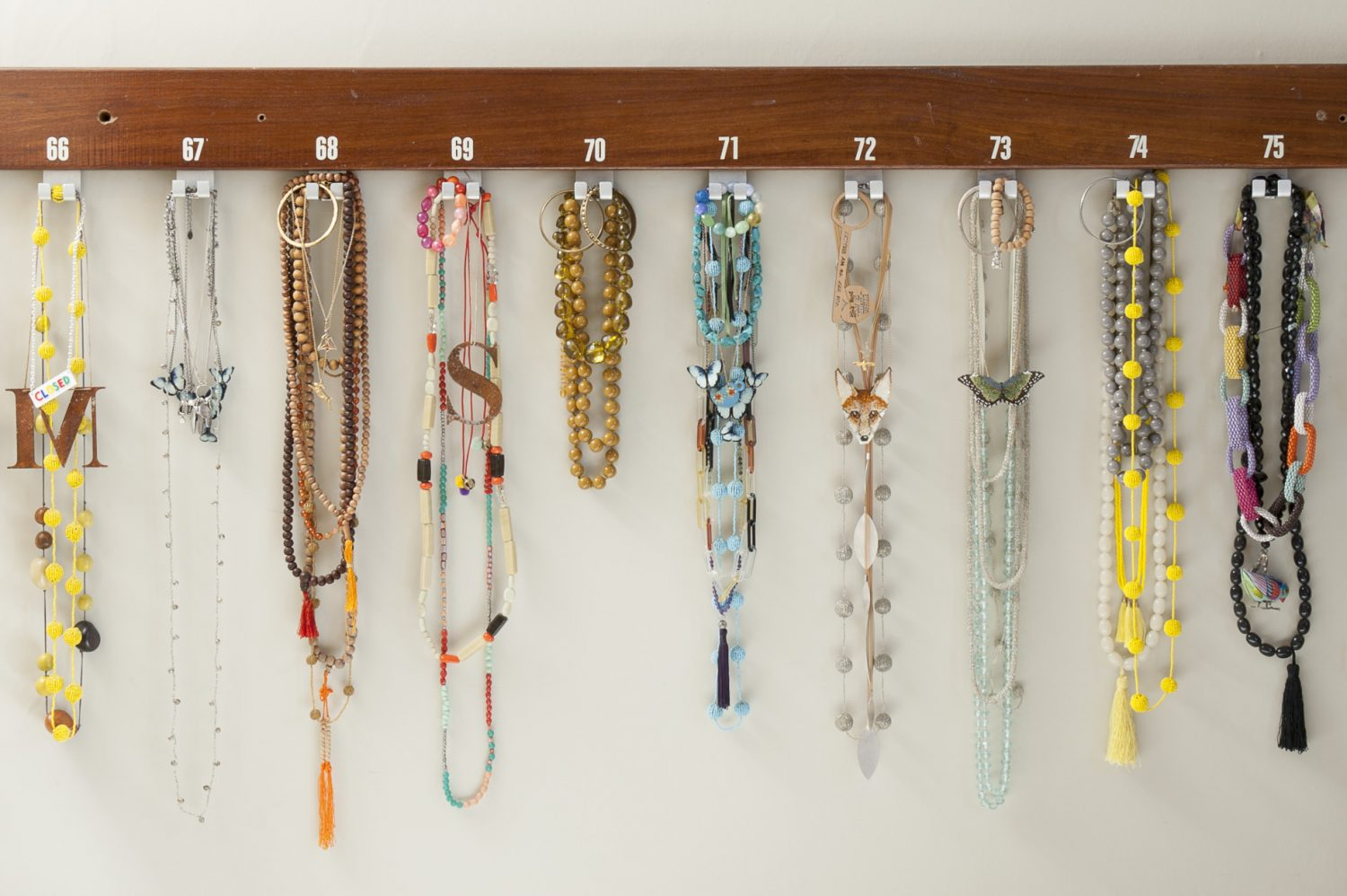Sarah's collection of necklaces hangs from a row of salvaged school coat hooks