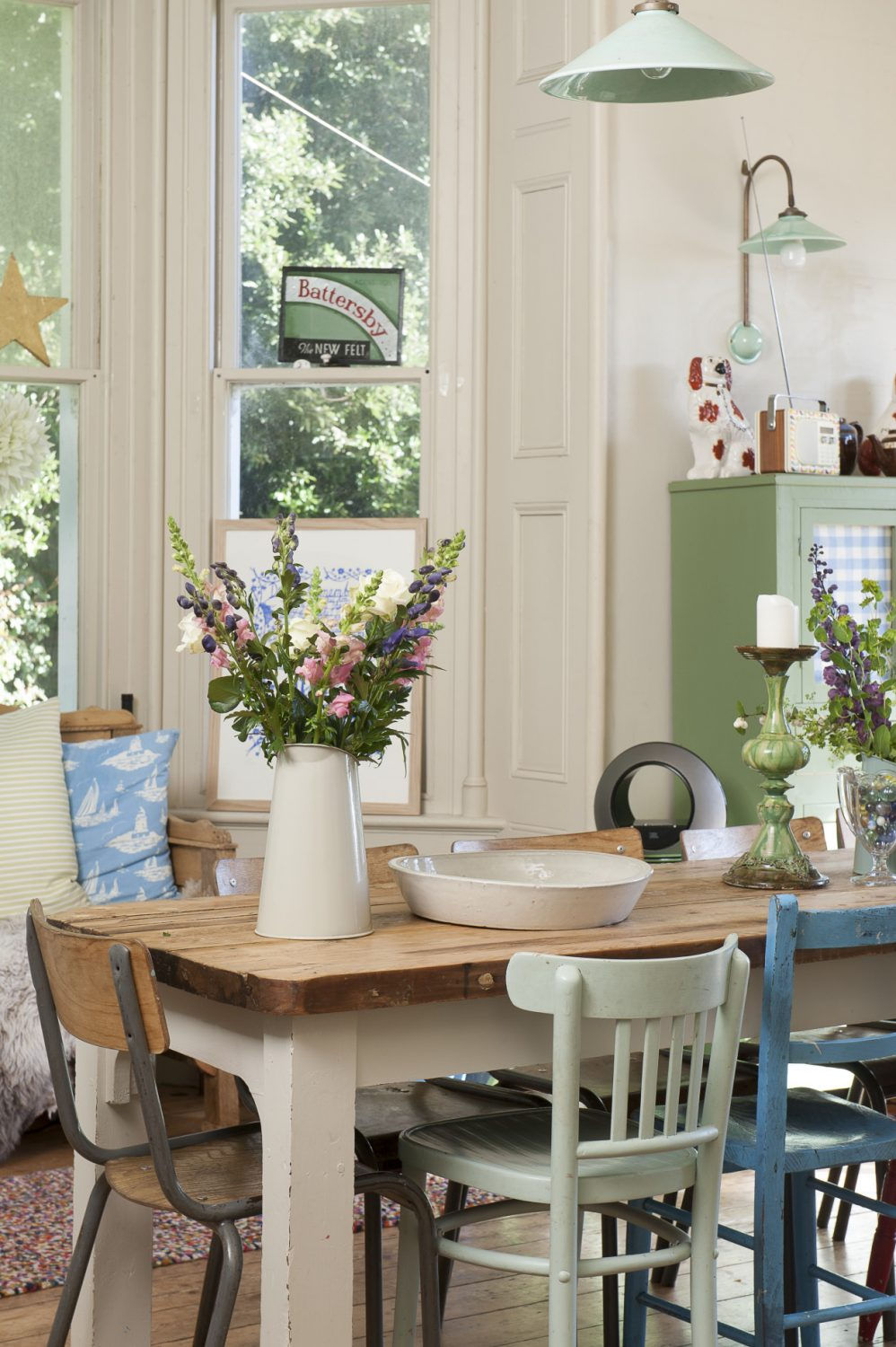 A verdigris coloured French rise and fall pulley light hangs from the very tall ceiling over a long, narrow, scrubbed wooden refectory table that has a collection of vintage school and bentwood chairs around it and a jug of simple English garden flowers at one end