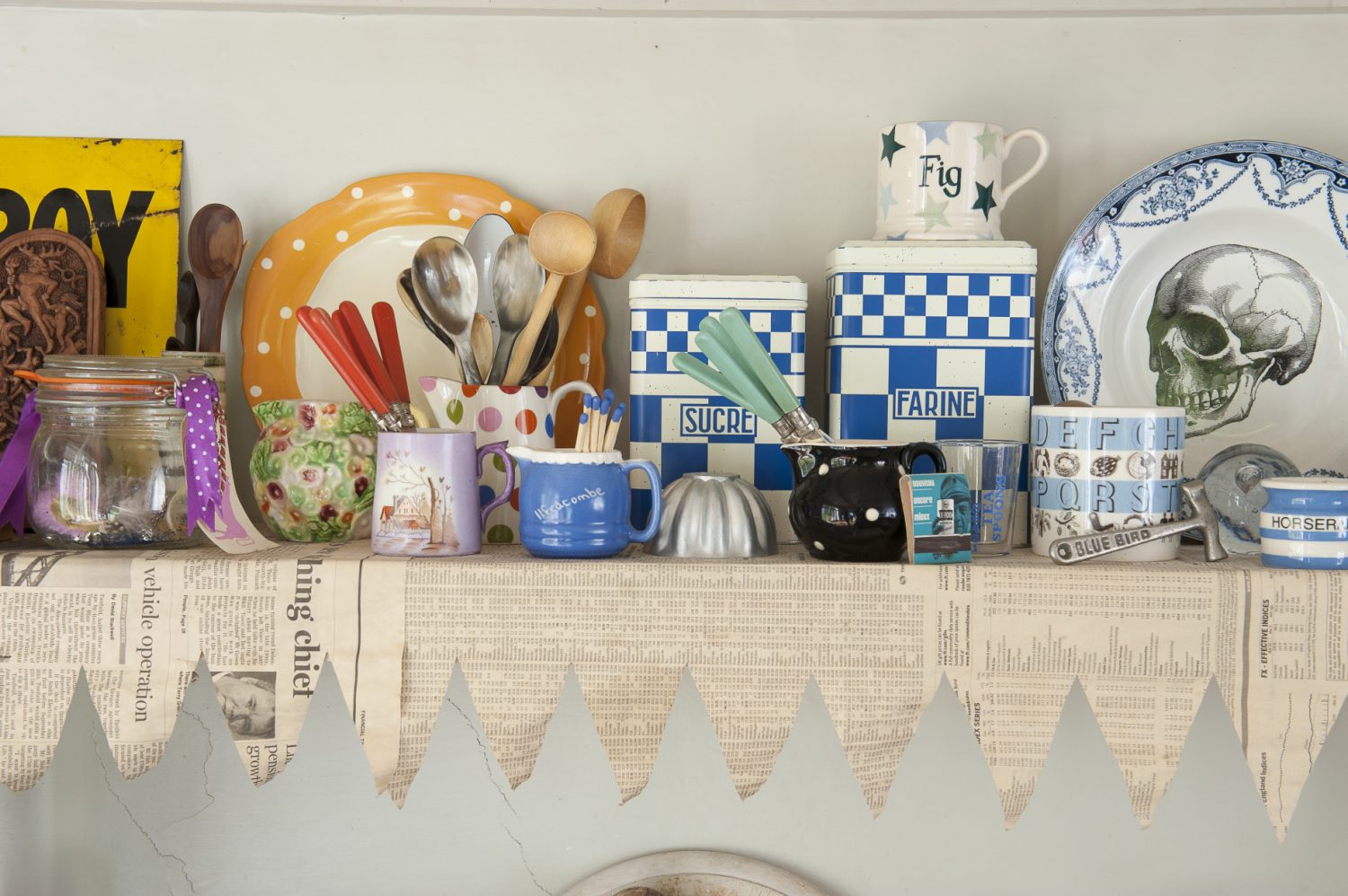 Above the old-fashioned, porcelain sink, shelves that support a collection of Cornish creamware have been lined with newspaper with a precisely cut zigzag edge, so that it looks like bunting
