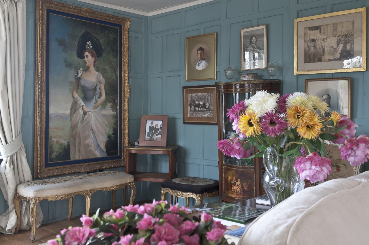 The panelled walls of the drawing room have been painted ballroom blue which perfectly offsets the gilt framed portraits around the room