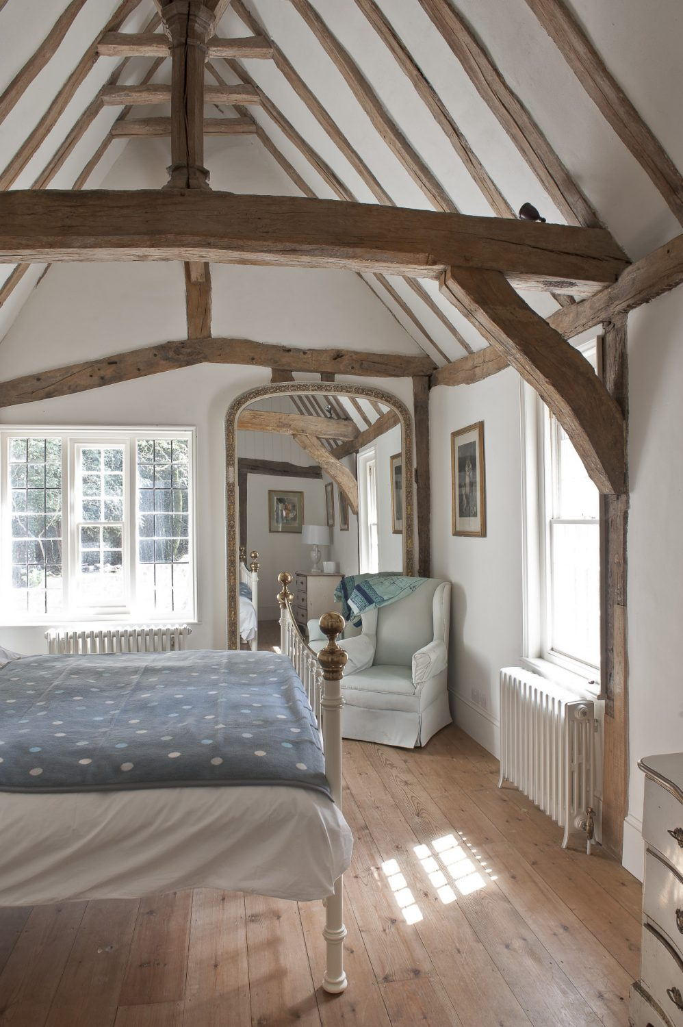 The room beyond is the bedroom where the warm, honey coloured timbers are offset by fresh blue and white linens on the bed and armchair
