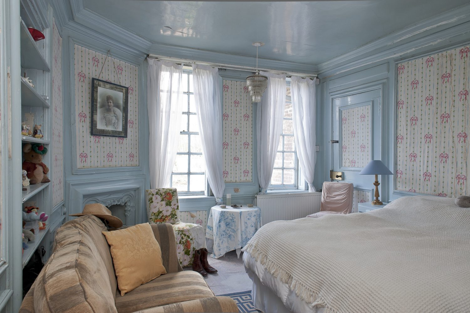 Olga's old night nursery is an almost perfect capsule of late 19th century interior design, the woodwork on the panelled walls is painted pale powder blue and in between, the wallpaper features tiny yellow rosebuds with pink ribbons running between them