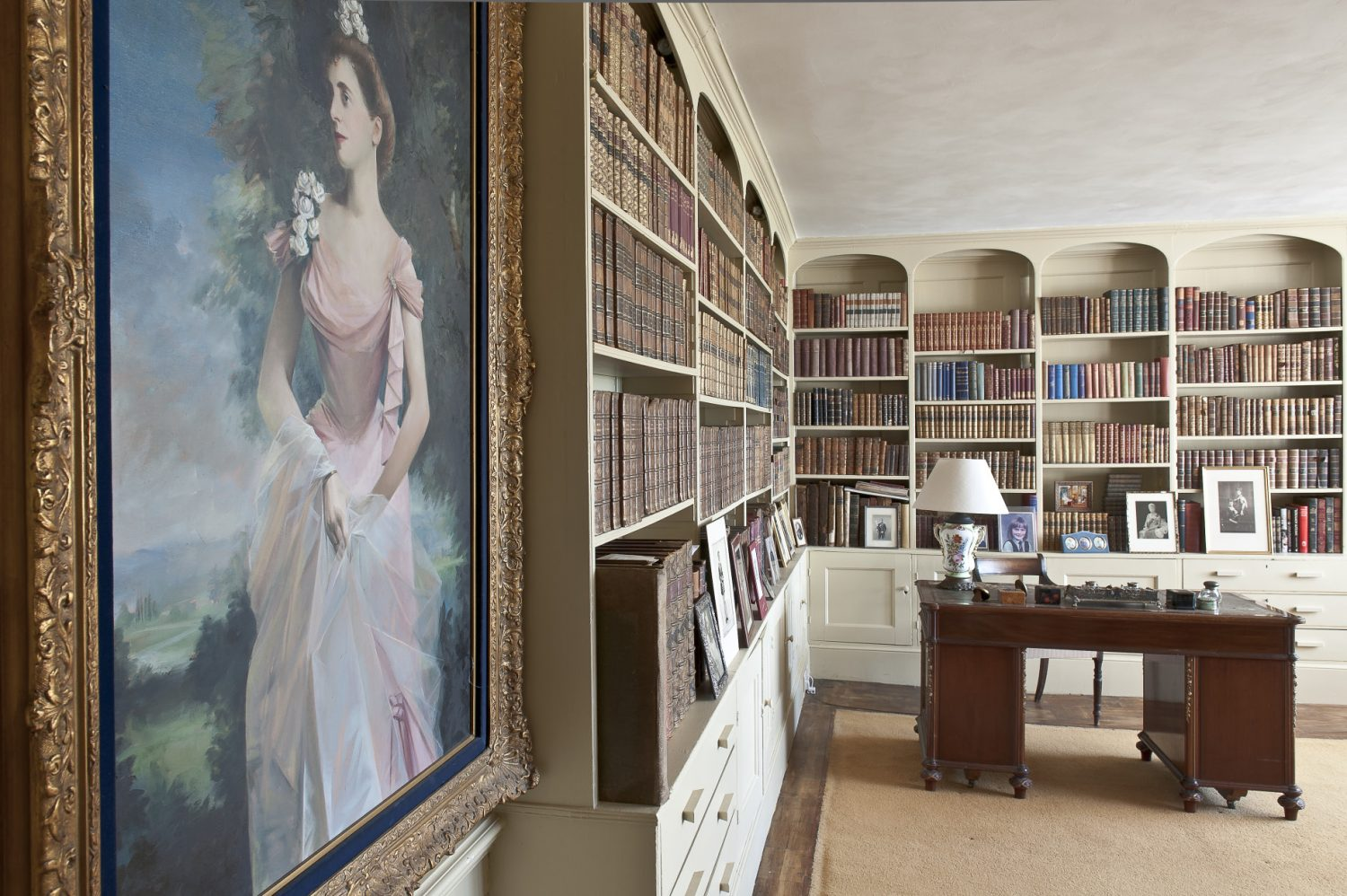 The library walls are painted a soft ochre yellow and two sides of the room feature floor to ceiling cupboards and shelves that support hundreds of leather-bound books.