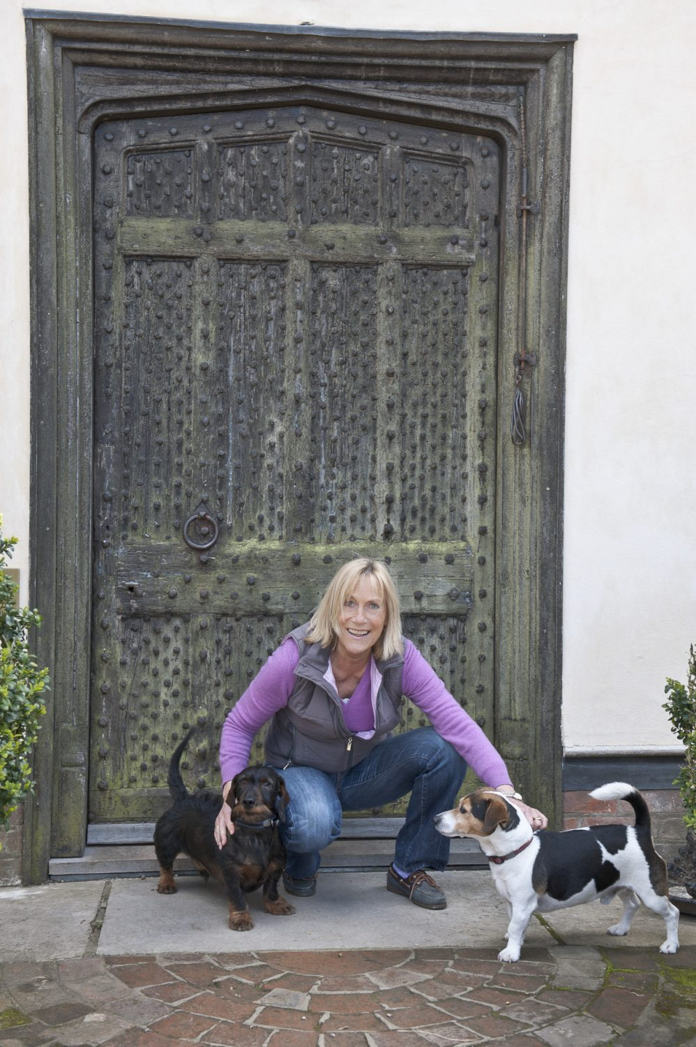 Olga, with Jak the Jack Russell and Ronny the Dachshund, outside Provender's heavy front door which is studded with large iron nails