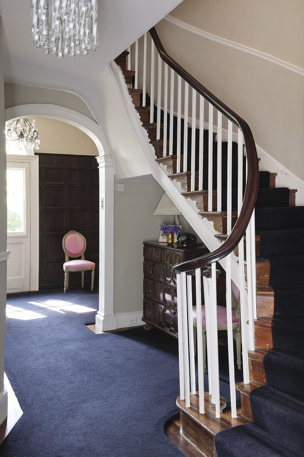 The hallway has been painted in a warm grey with a charcoal coloured carpet that is also used as a runner on the staircase that twists in classic Georgian style. Under the stairs is an oak and walnut chest of drawers bought from Strand Antiques in Rye