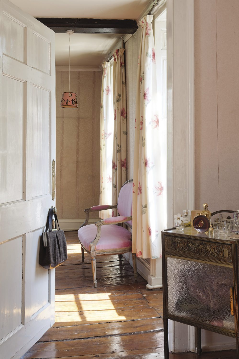 A door from Gabby and Russell's bedroom leads to a dressing room with a glass and metal table where Gabby keeps her perfume bottles and small accessories