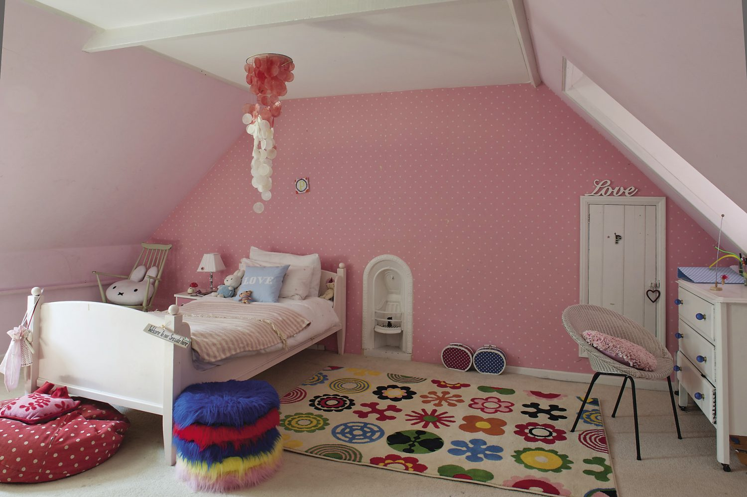 The older girls' rooms are up another flight of stairs in the eaves of the house and decorated in cheerful shades of pink, blue or orange