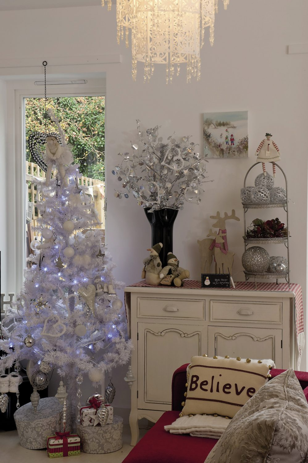 A console table is covered with a red and white gingham runner and a three-tiered sweetmeat stand displays a collection of large baubles as well as a red and white stripy-stockinged peg doll