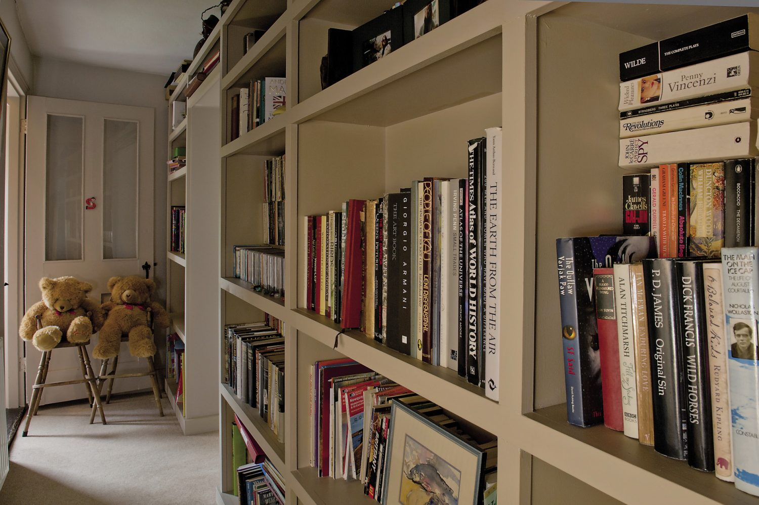 A bookcase groaning with books lines the corridor to one of the children's bedrooms
