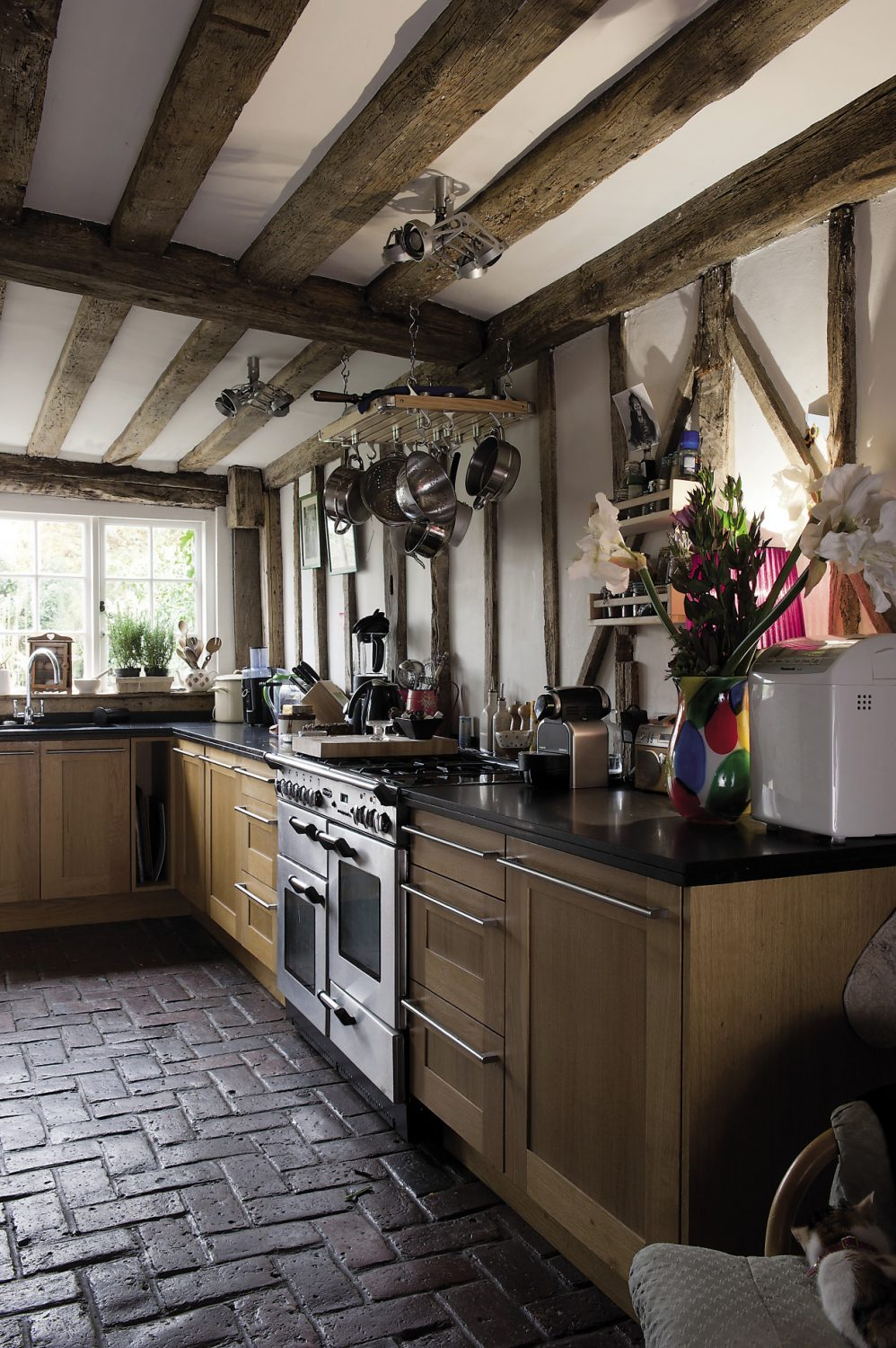In the kitchen, carpenter Mick has worked his magic with bespoke oak shelving and cabinets that look for all the world like mahogany but are, in fact, artfully painted MDF