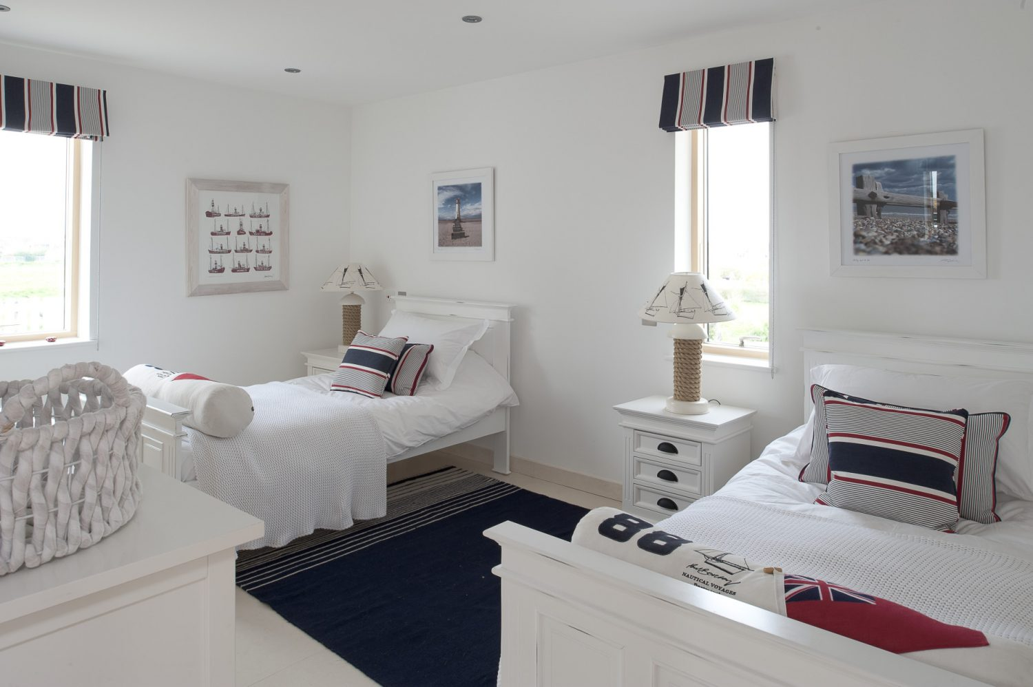 Downstairs, a corridor leads to a twin bedroom with white sleigh beds, knitted covers and red, white and navy blue striped blinds and cushions