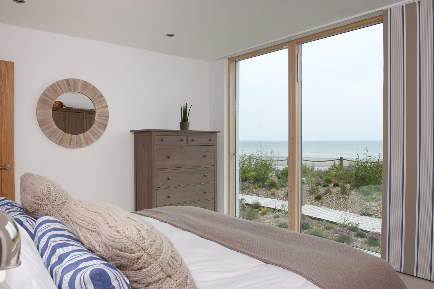 In the other wing another guest bedroom, facing the sea, is decorated in softer shades of taupe, ecru and slate blue