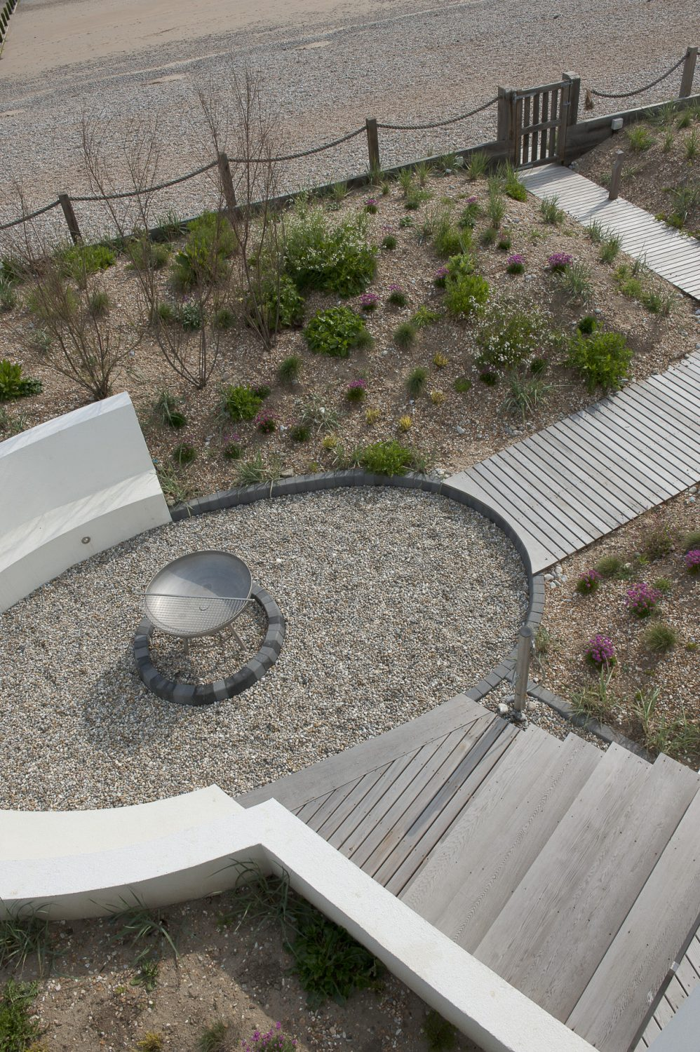 Sea Gem's garden was designed by Kent-based Jo Thompson, who has recently created an award-winning garden at Chelsea Flower Show. Curving wooden boardwalks snake through the grasses and a fire pit is surrounded by a sunken area of seating that is invisible from the beach and so offers both shelter and privacy