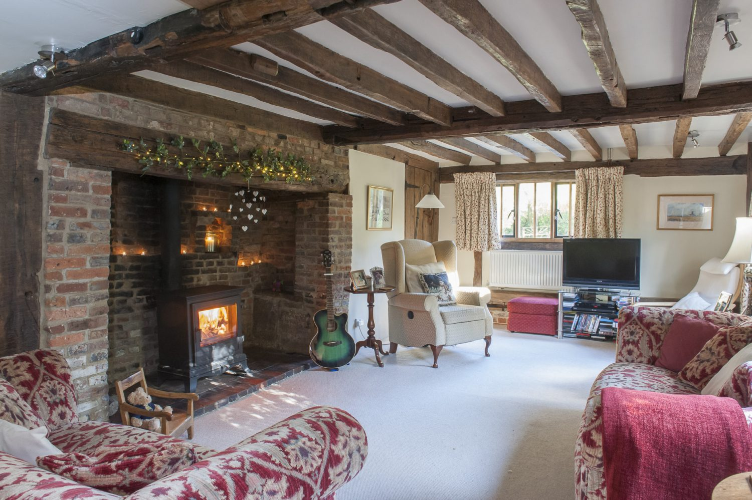 In the sitting room, the second inglenook fireplace shows clearly where the floor has been lowered. Two comfortable tapestry sofas in rich plum tones, complement delicately patterned curtains made by Bell House Fabrics