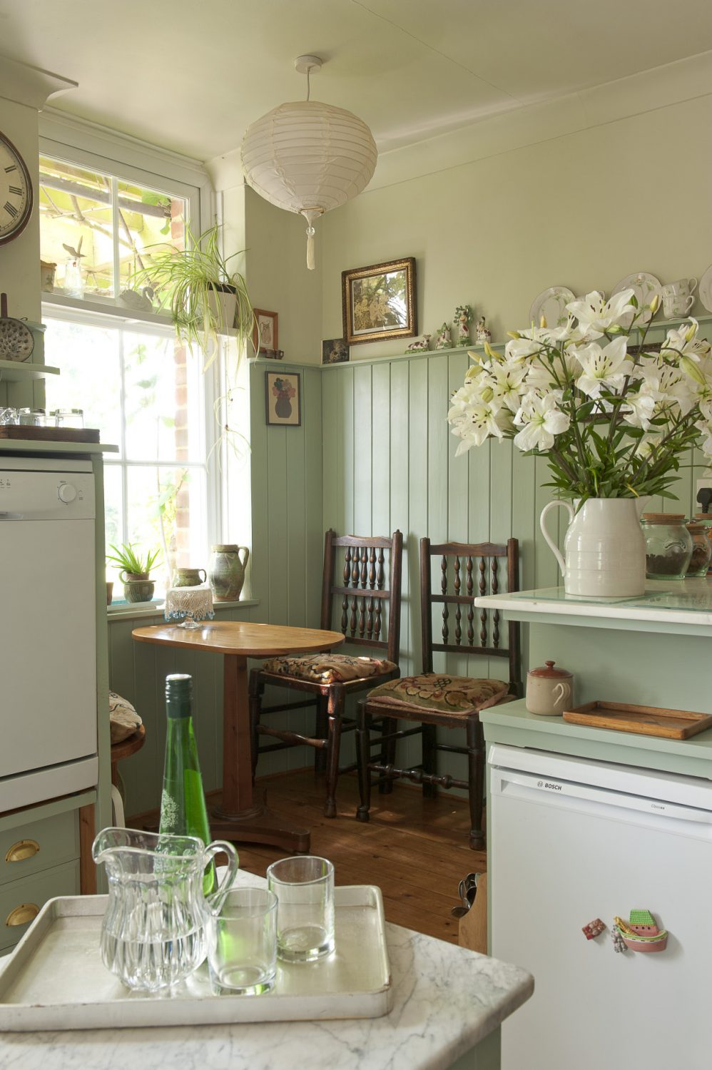 A little alcove breakfast table for two is nestled in one corner of the modest-sized shaker-style kitchen