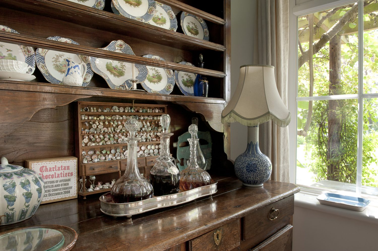A miniature wooden dresser, filled with Jenny's doll's house pottery stands centre stage amongst the full-size crockery in the drawing room