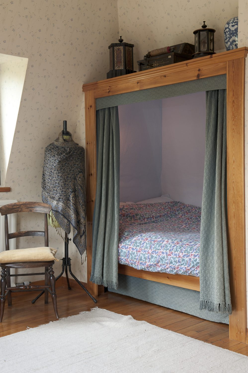 A double bed is tucked secretly behind a pair of curtains