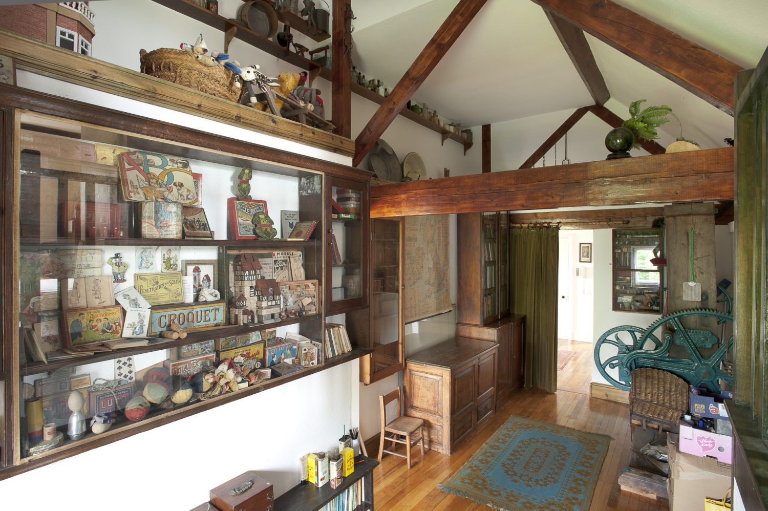 Upstairs a secondary hallway, home to an old hop press, has walls festooned with old farm tools, cabinets filled with children's games and writing and drawing tools