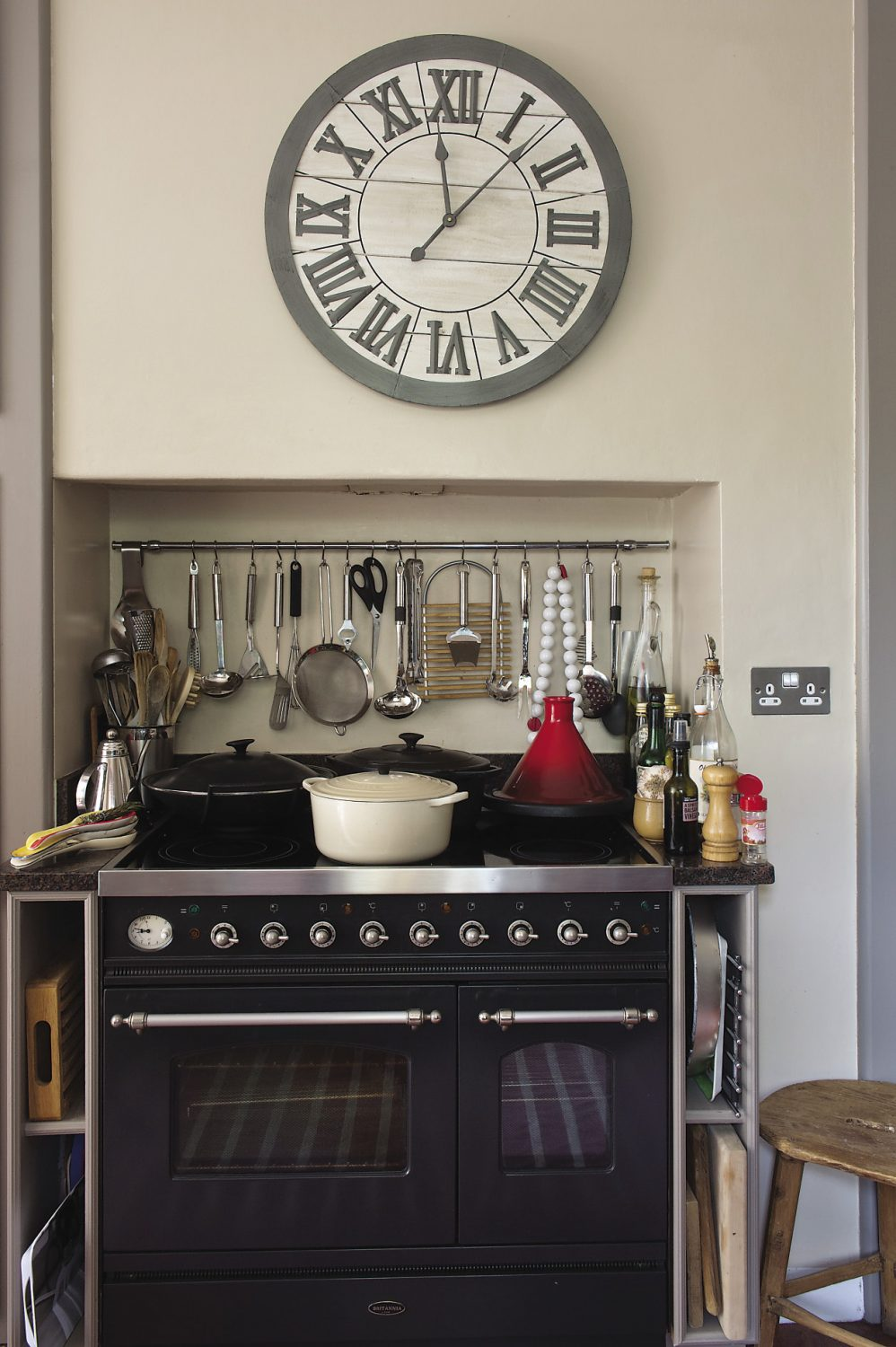 A large wooden clock with bold Roman numerals that was bought from Maison in Tunbridge Wells hangs above the wide black cooking range