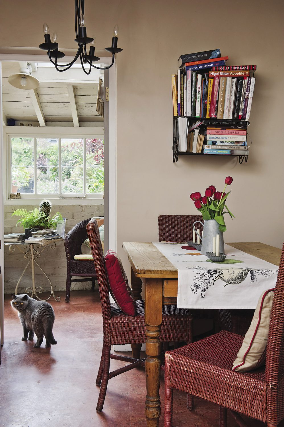 Wicker chairs surround the wooden table in the kitchen area. Above it, metal shelves house Ann's collection of cookery books